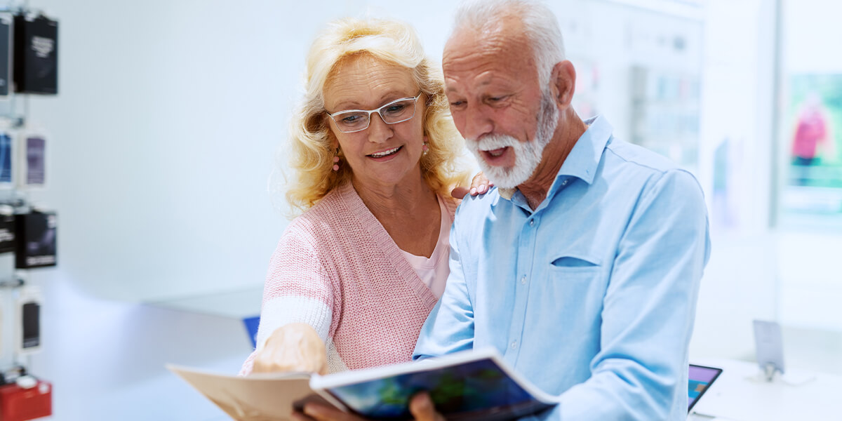 Happy senior couple looking at catalog in store